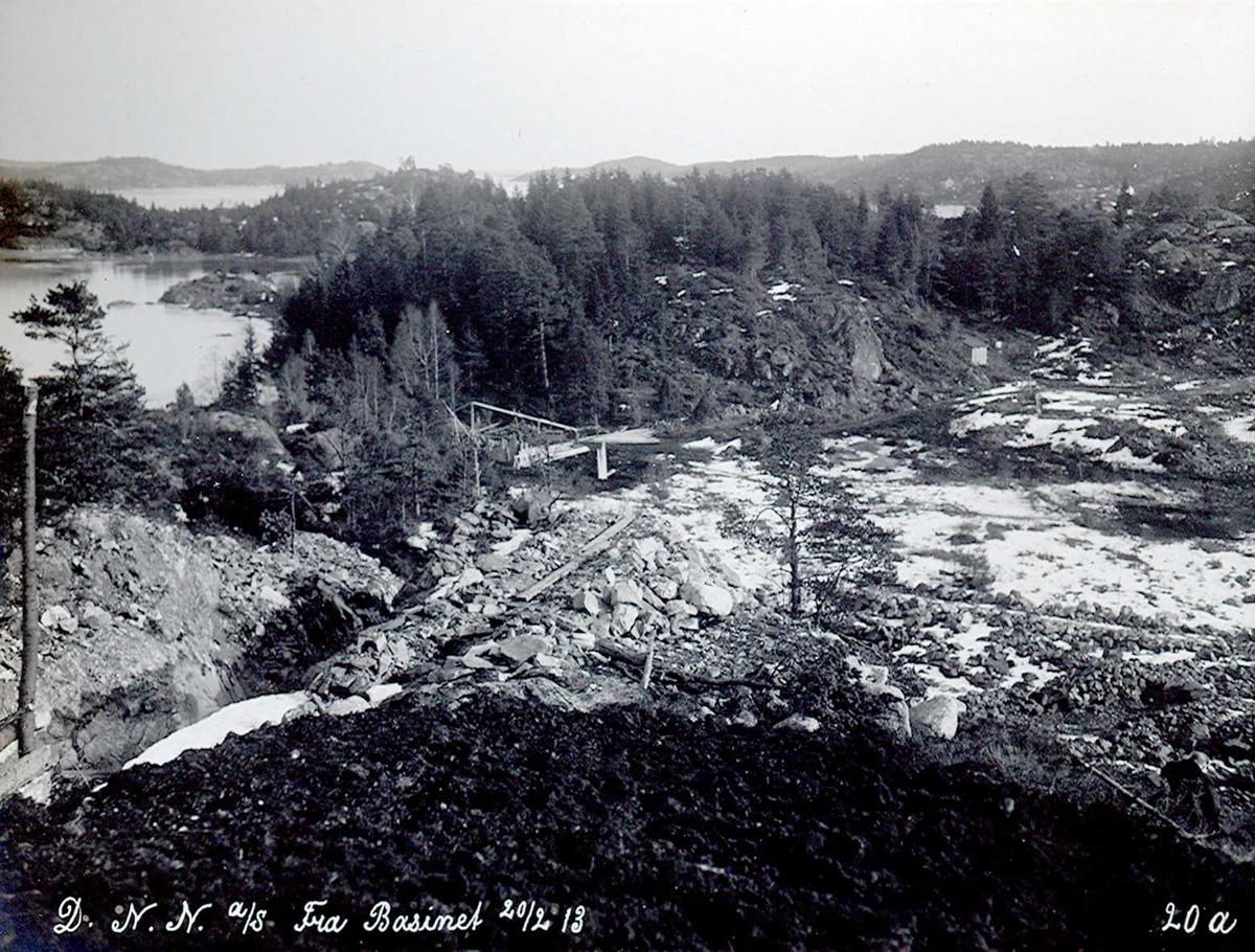 """""""20/02-1913"""" Nitriden. Vannledningsgrøft opp til høydebassenget. Fabrikktomten til høyre. Til venstre Heggedalsbukten og noe av Buøy. Tromøysund og Tromøy helt til høyre. I det fjerne til venstre Hvideberget."""