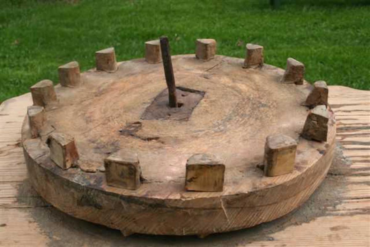 Treplate med gjennomgående jernpigg som fungerer som aksling for rund treskive med 14 knaster. På begge sider av treskiven er det montert jernbeslag omkring akslingshullet. Spor etter smøring med tjære.