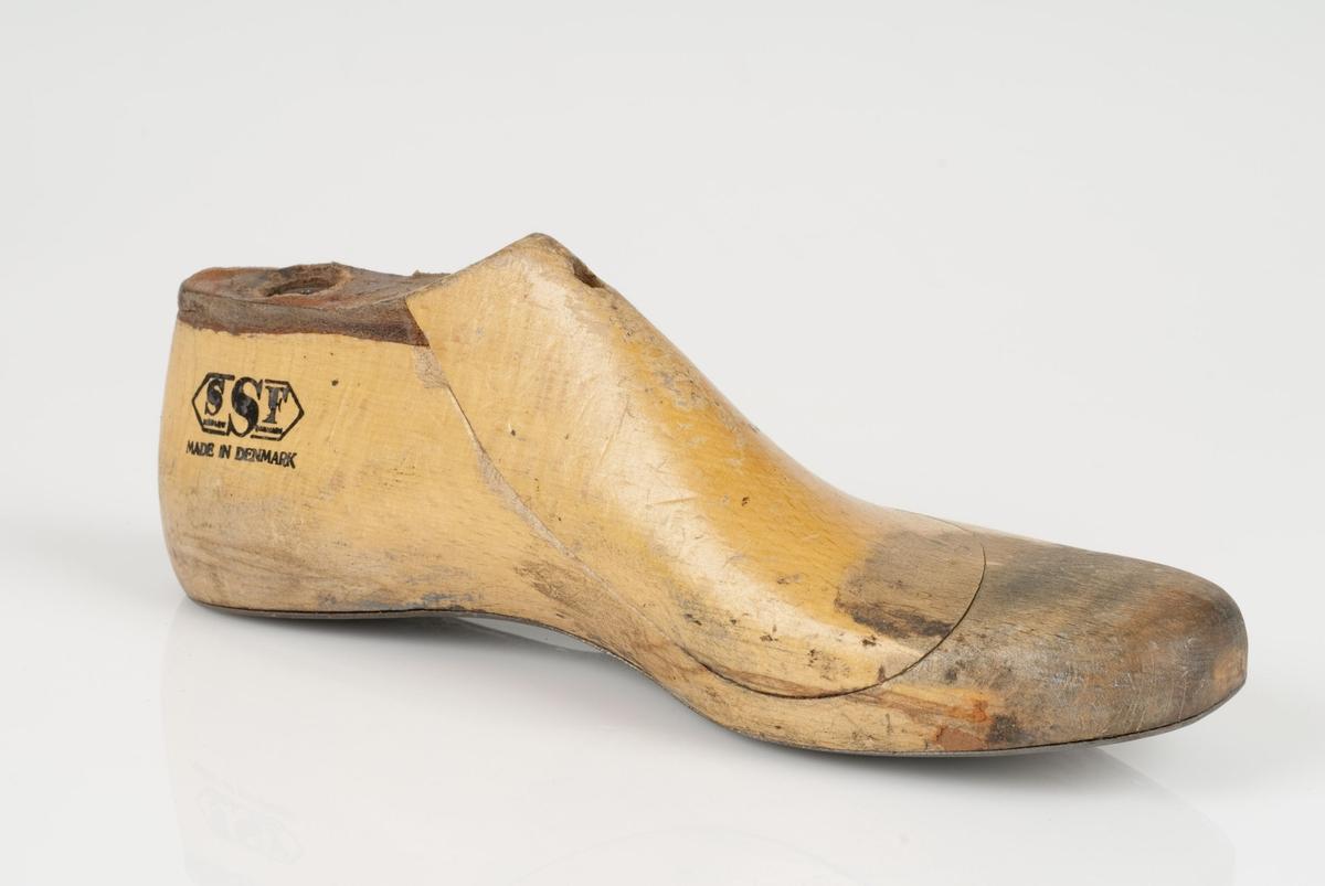 En tremodell i to deler; lest og opplest/overlest (kile). Venstrefot i skostørrelse 38, og 8 cm i vidde. Såle i metall.