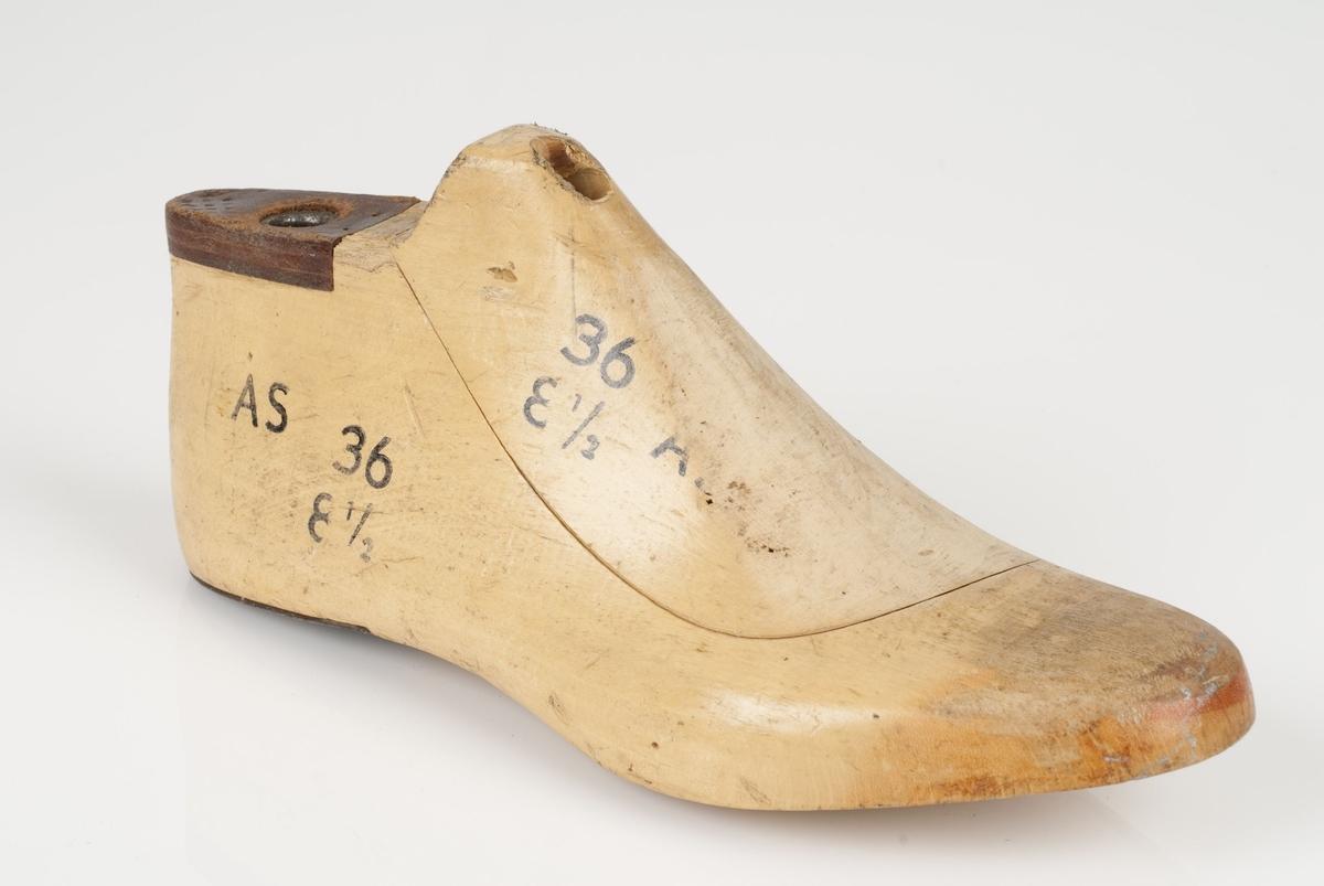 En tremodell i to deler; lest og opplest/overlest (kile). Høyrefot i skostørrelse 36, og 8,5 cm i vidde. Lestekam av skinn Hælstykket av metall.