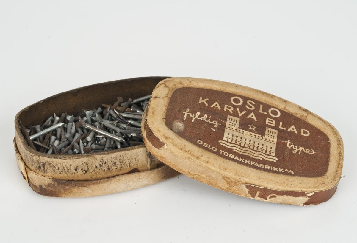 Forskjellige typer spiker av stål i en tobakkseske av papp.