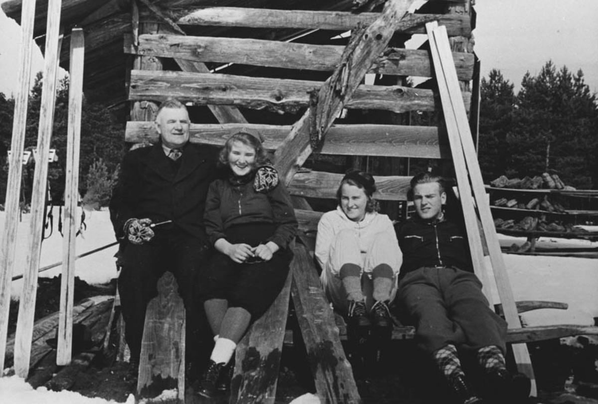 """Fire personer ved en torvhytte på """"måsan""""."""