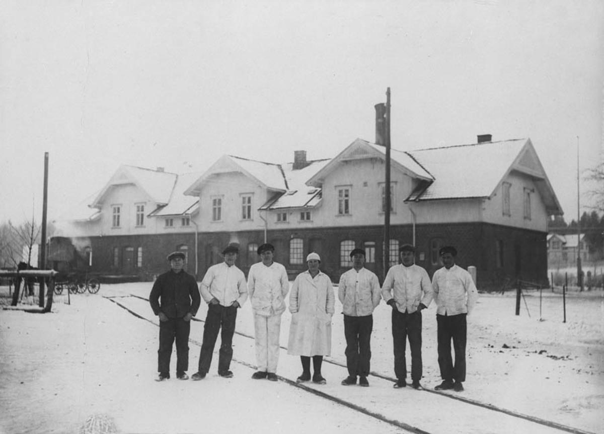 7 meieriarbeidere på sidesporet foran meieriet.