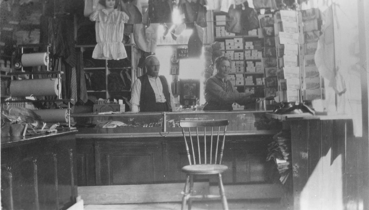 Interiør manufakturbutikk, et par bak disken. Herman Grøn-Hansen til venstre.