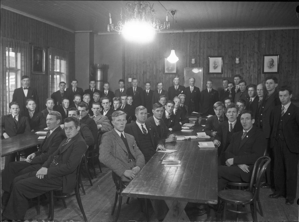 Forsamling menn. Bilder av ordførere på veggene.