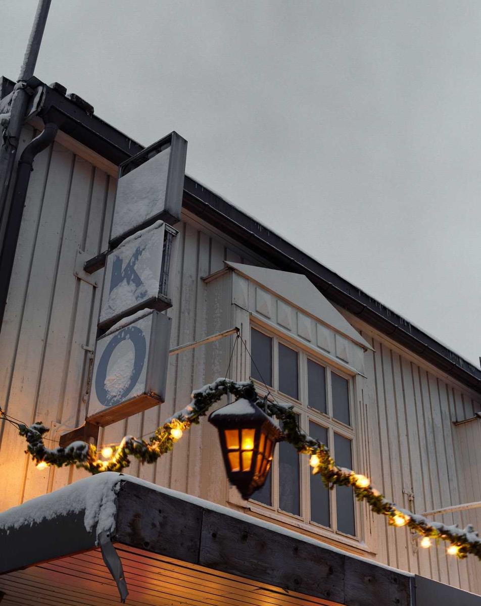Julebelysning.  Hvite lys i grangirlander med røde lykter på forretningsbygg.