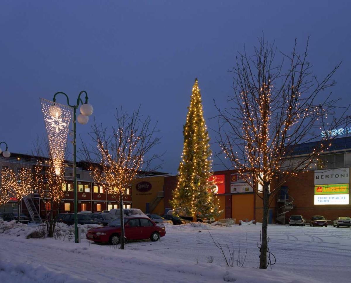 Julebelysning.  Juletre på parkeringplads ved Strømmen Storsenter. hvite lyslenker som henger nedovertreet. Hvite lyslenker i treer langs veien og lys i kremmerhusform på lyktestolper
