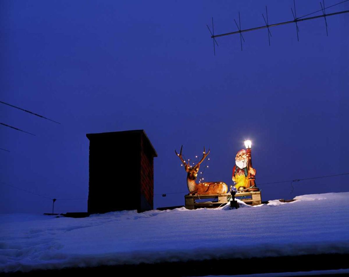 Julebelysning  Reinsdyr med lyslenke og nisse med lysende lykt på taket av enebolig