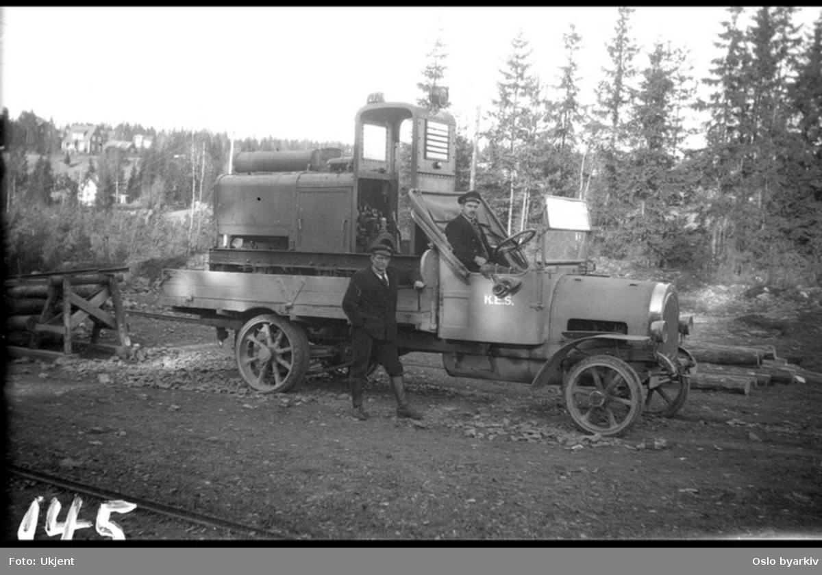 På lastebilen står et smalsporet anleggslokomotiv, bygget av Levahn i Kristiania. Lastebil merket K.E.S. (Kristiania Elektriske Sporvei) med sjåfør og mann ved siden av. Fra arbeidet med forlengelsen av Lilleakerbanen til Bekkestua og Haslum, ferdig 1924.