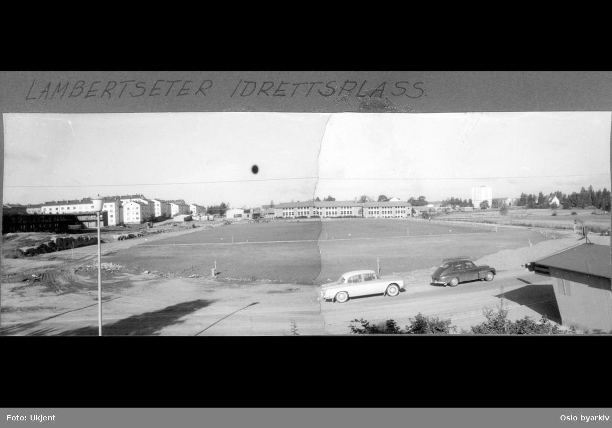Friidrettsfeltet på Lambertseter stadion under fullførelse. Biler og kiosk ved med lysreklame for Cola og Solo ved Feltspatveien. Lambertseter skole, blokkbebyggelse i Glimmersvingen og høyblokka på Lambertseter senter i bakgrunnen.