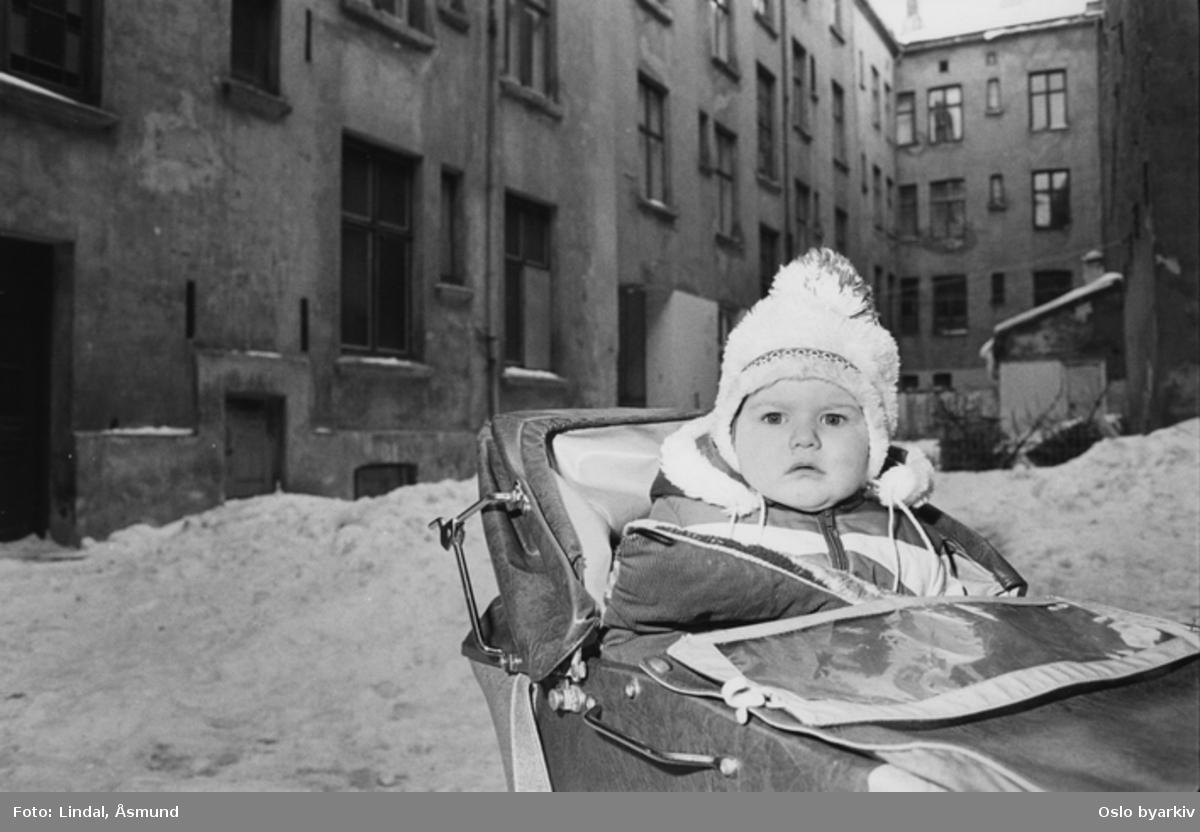 Barn i barnevogn i forfallen bakgård vinterstid. Fotografiet er fra prosjektet og boka ''Oslo-bilder. En fotografisk dokumentasjon av bo og leveforhold i 1981 - 82''. Kontakt Samfoto ved ev. bestilling av kopier.