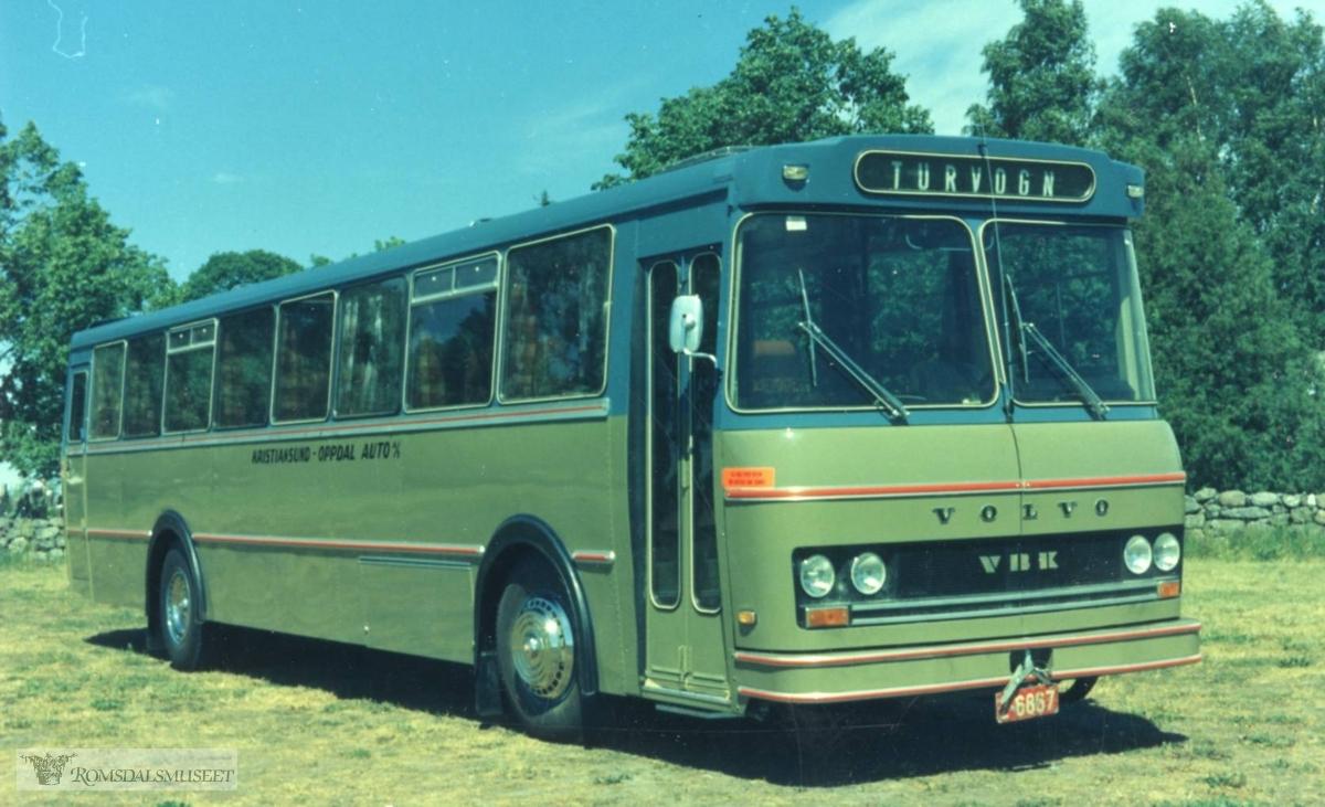 Kristiansund - Oppdal Auto..I følge Oddbjørn Skjærsæters notater er dette bildet fra 1975 og er tatt ved Borre kirke som ligger like ved Vestfold Bil og Karosseri (VBK) der bussens karosseri ble bygd. Bussen ble levert til Kristiansund-Oppdal Auto (KOA) og registrert i juli 1975 på nummer UX19535 og den fikk internnummer 59 hos KOA: En juni samme år fikk KOA en identisk buss med registreringsnummer UX19380 og internnummer 58. Modellen er Volvo B58 og hadde 46 sitteplasser. Begge bussene ble satt inn i rutene Oppdal-Sunndalsøra-Tingvoll- Kristiansund..(fra Oddbjørn Skjørsæter sine samlinger i Romsdalsarkivet)