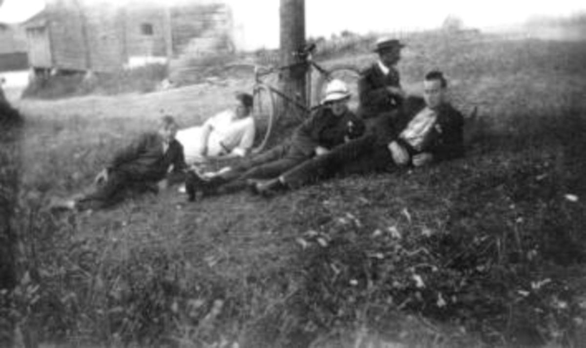5 ungdommer med sykkel. Gammel tømmerbygning i bakgrunn.