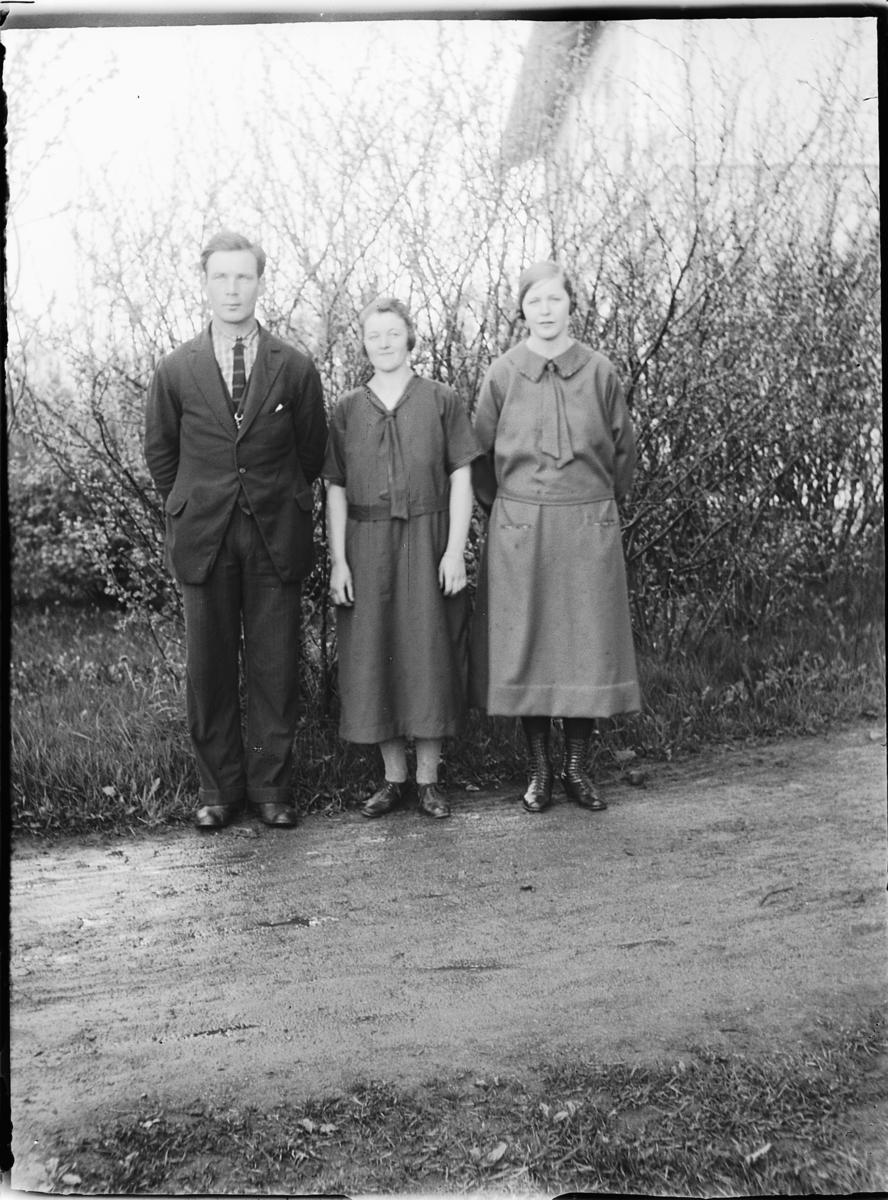 Tre ukjente personer, mann og to kvinner, langs en vei.
