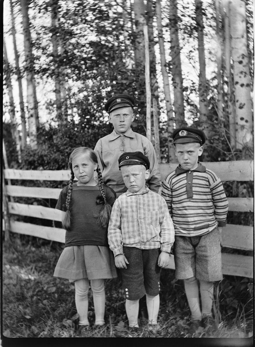 Ei jente og tre gutter med luer ved et gjerde.