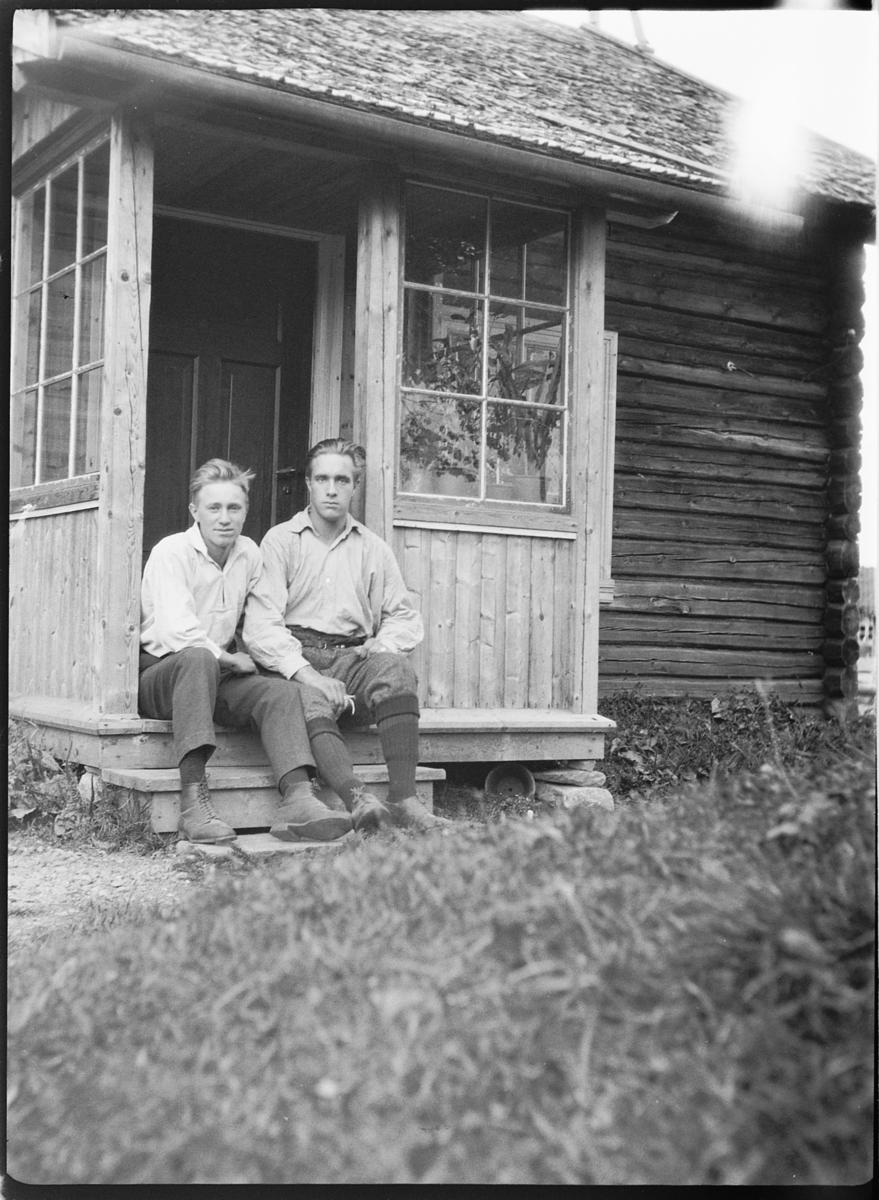 To menn på trappa ved inngangsdøra til et hus.