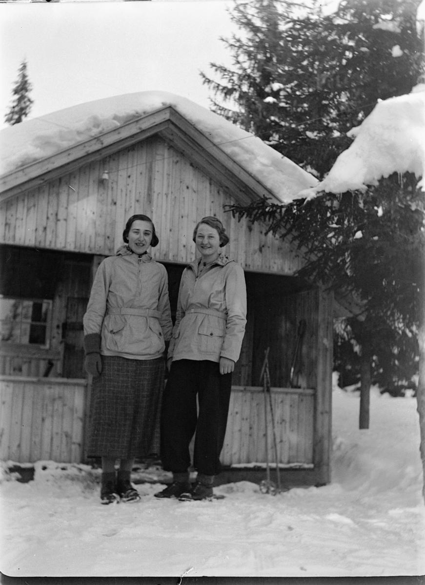 To kvinner foran ei HYTTE i skogen.