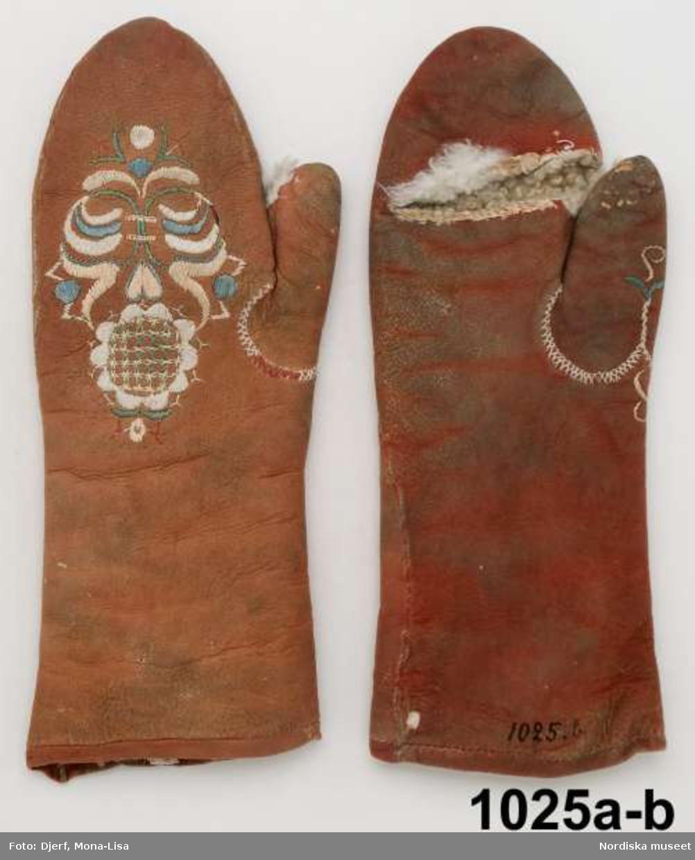 Ett par tumhandskar av brunrött sämskskinn med vitt ludet fårskinnsfoder. Öppning på handens insida för fingrarna  samt i tummen. Blombroderi på handens översida  i plattsöm, stjälksöm och bottensöm med silke i pastellfärger, rosa, ljusblått, vitt och grönt, Blekta, på vissa ställen ser man att de varit mycket rödare. Sådana silkebroderade handskar ingick i de standardgåvor som fästmannen köpte och gav sin blivande brud. Samma mönster kan finns på flera av dem, jfr. 713, 10748. Slitna. /Berit Eldvik 2013-03-11