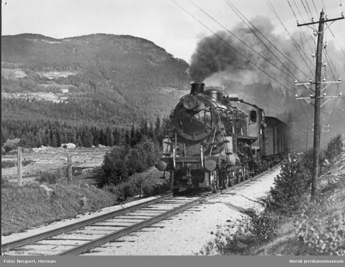 Et damplokomotiv av type 26c under full damp med tog i Hallingdal