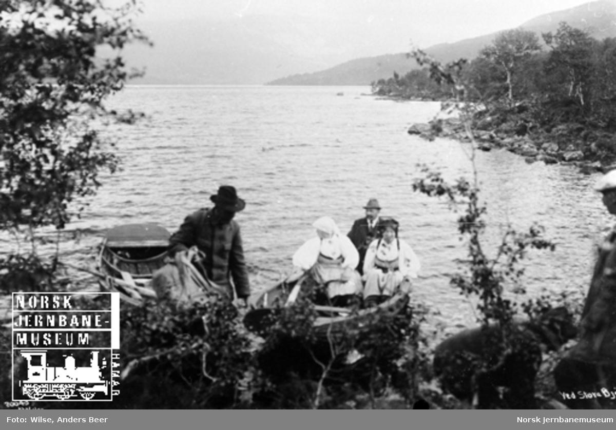 Fem personer, hvorav to kvinner i bunad, med robåt på Store Bjørnevatn i Setesdal