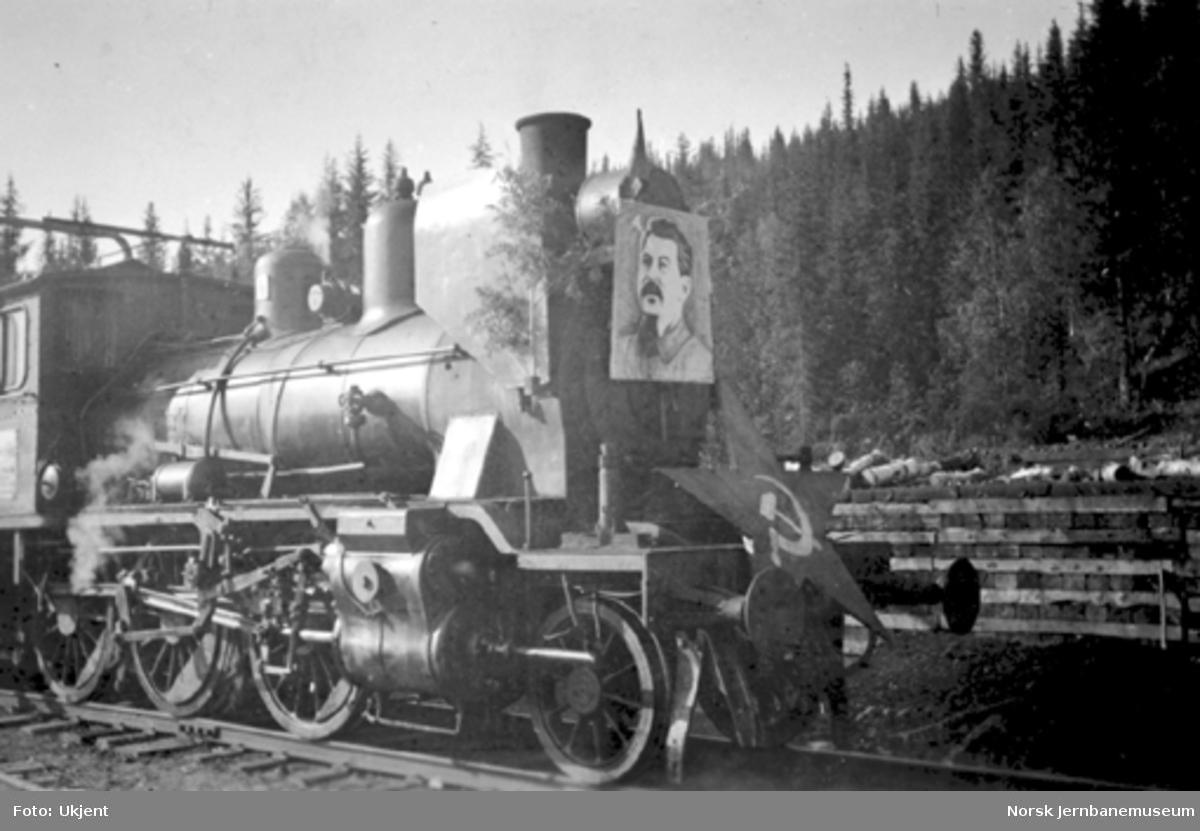 Damplokomotiv pyntet med bilde av Stalin og det russiske flagget i tog med frigitte russiske krigsfanger på Grønfjelldal stasjon