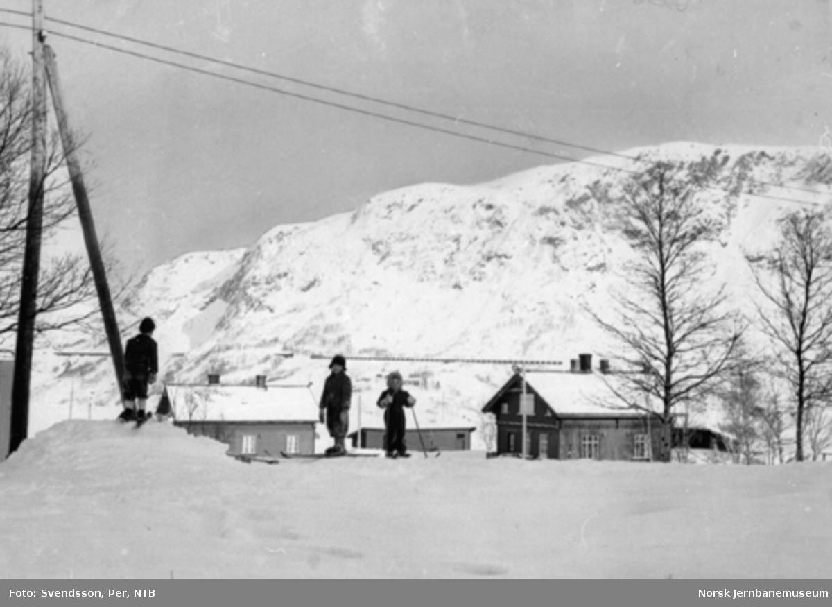 Barn på ski på Katterat med utsikt mot østgående malmtog i bakgrunnen