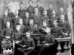 Gruppebilde med 21 telegrafistelever rundt et bord med teleg
