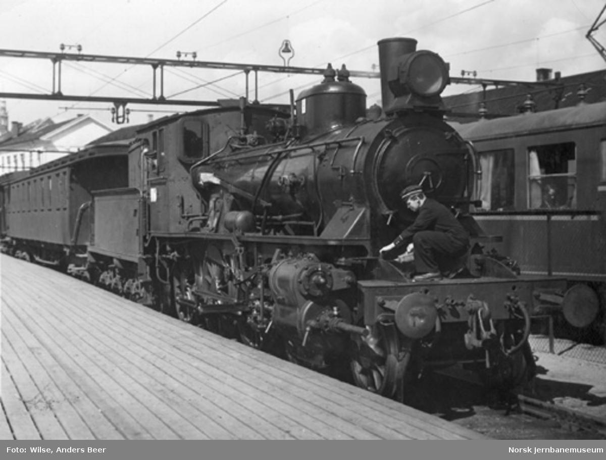 Damplokomotiv type 27b nr. 369 foran persontog på Oslo Østbanestasjon : fyrbøteren eller lokomotivføreren er i gang med smøring