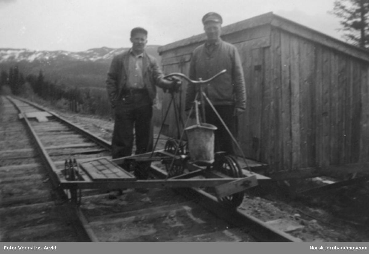 Baneformann Sigurd Vennatrø og en ukjent person stående ved en smalsporet dresin ved linjevisitasjon