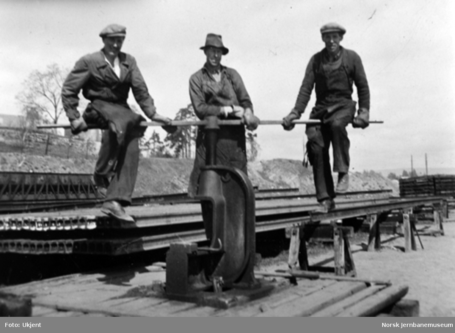 Tre banearbeidere ved en skinnepresse