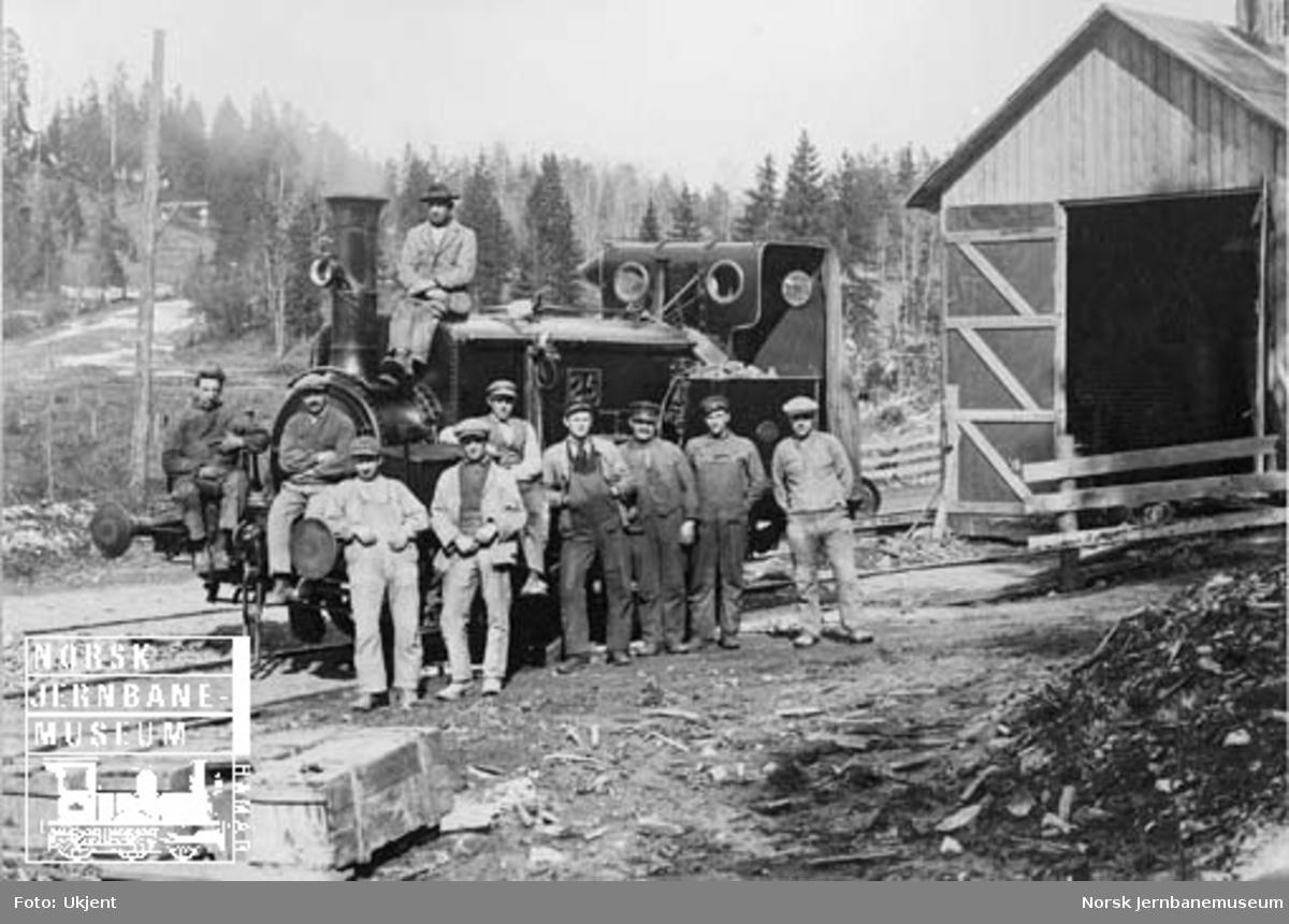 NHJ damplokomotiv litra D nr. 25 med anleggsarbeidere på Bærumsbanens anlegg, fotografert utenfor lokomotivstallen som trolig var på Øraker