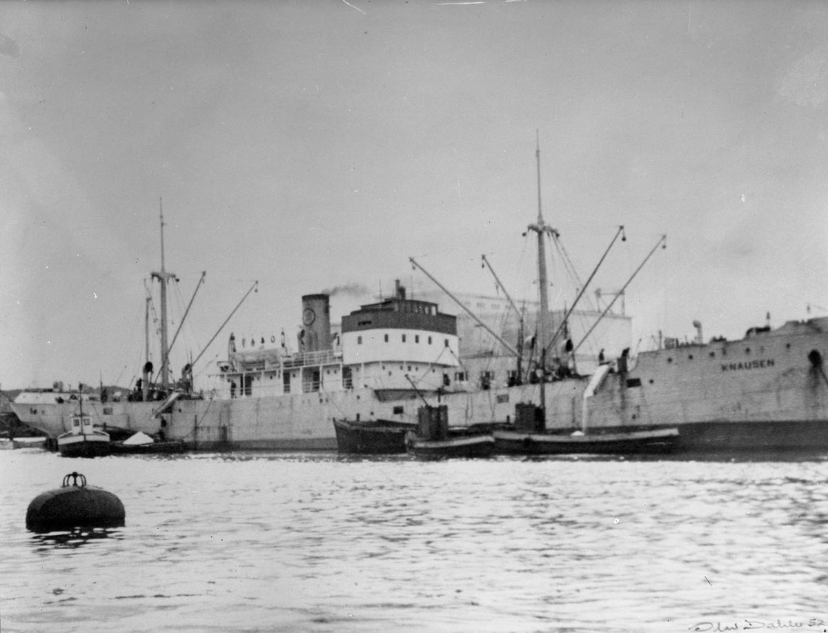 """Dampskipet D/S """"Knausen"""" ved kai. Deler av mannskapet på akter og dekk. Flere mindre båter like foran skipet.  Hus i bakgrunnen."""