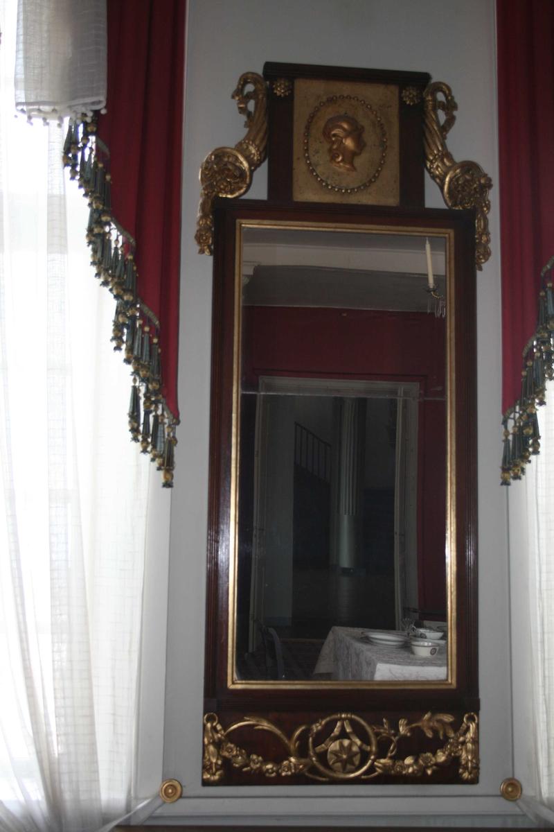 Rektangulært speil med forgylte ornamenter. Toppstykke med medaljong med kvinnehode, overflødighetshorn. Girlandere nederst. Speilglasset er delt i to.