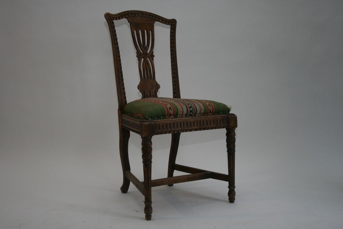 En av to stoler, Sheraton. Bjerk, utskåret rygg, sarg og ben. Trekk grønt m/striper i rødt, grått og grønt. Stolen kan være fra slutten av 1800-tallet.