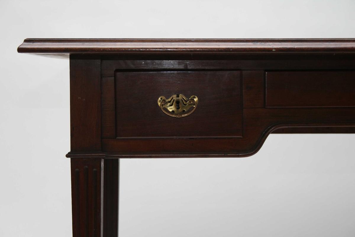 Skrivebord i mahogni, 3 skuffer, bordplate trukket med grønt lerret. Skuffene har håndtak og nøkkelskilt i messing. Kanelerte bein.