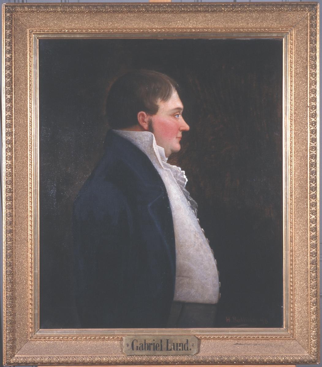 Portrett av Gabriel Lund Mann i profil, brunt hår og kinnskjegg, dobbelthake, mage.  Mørk kledning, lys vest m. knapper og lys skjorte med rysj