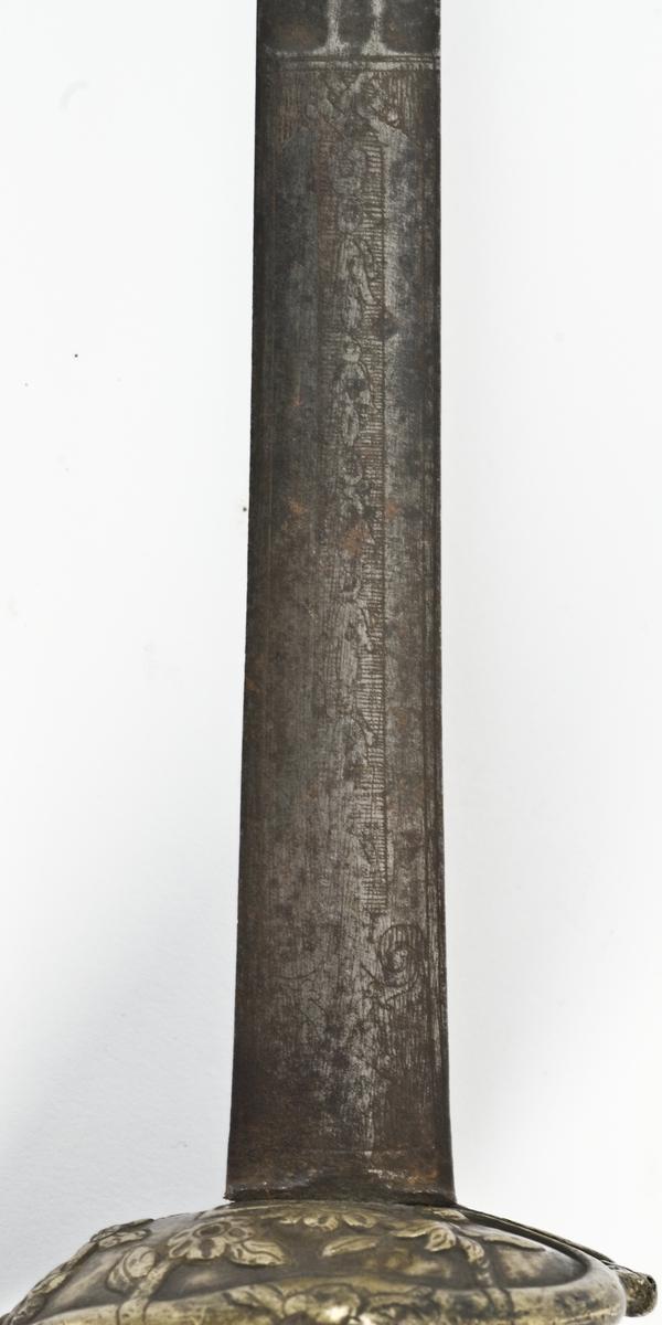 Plommeformet knapp med støpt grep. Skjellformet parerplate og bakre parerstang og håndbøyle mangler. Klinge med 6-kantet tverrsnitt, hvorav øvre deler elipseformet.  Rankedekor og stjerner på begge sider av klingen. Grepet har i sin helhet grener med blomsterdekor støpt i relief.   Nedre del av klingen er brukket.