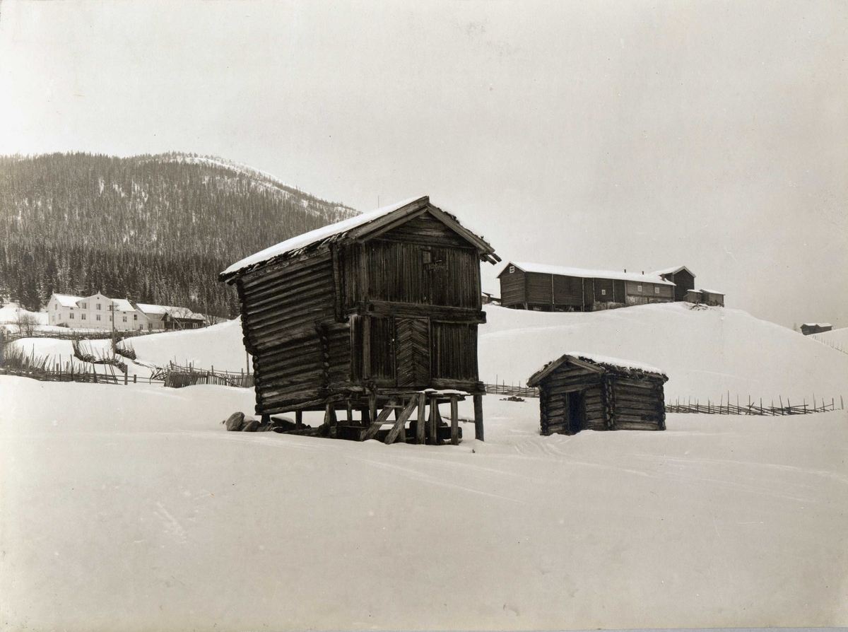 Den gamle prestegård. Øvre Rendal, Nord-Østerdal. Stabbur i snølandskap, låve og våningshus i bakgrunnen.
