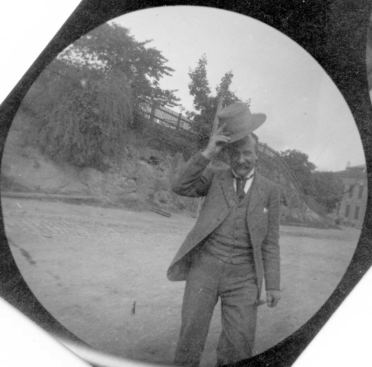 Hr. Fischer, bror til Petter Fischer står i park og letter på hatten.