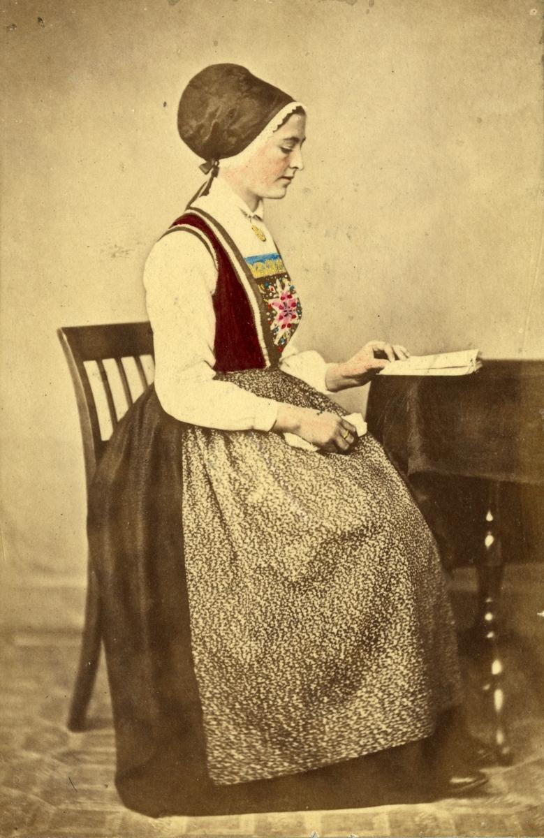 """12. Kvinnedrakt, konedrakt, sommerdrakt, fra Lavik, Høyanger. Portrett av sittende kvinne med hodeplagg i fotoatelier med nøytral bakgrunn og mønstret gulvteppe. Hun leser i en bok. Håndkolorert. Fra serien """"Norske Nationaldragter"""" (nr.12), fotografert av fotograf Marcus Selmer (1819-1900), Bergen."""