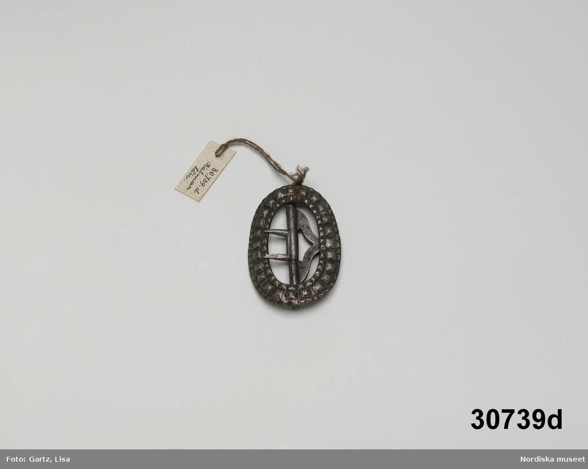 """Huvudliggaren: """"a-e, Spännen. från Kalmar län. Af silfver. Ink. gm friherre Emanuel Cederström [...]. 1/5 1881""""  b) """"Sölja, silfver, förgyld. H. 3,4 cm, Br 2,5 cm. Stämpel saknas. Frånsidan oförgyld."""" c) """"Sölja, Silfver, förgyld, gjuten. H 3,6 cm, Br 2,6 cm. Stämpel saknas. Frånsidan oförgyld.""""  A:1-2 Fyrkantigt halslås, helt förgyllt eller möjligen av mässing, graverad dekor i 1700-talsstil med punsad kant. Fäste för 3 kedjor som alla saknas. /Berit Eldvik 2007-02-27"""