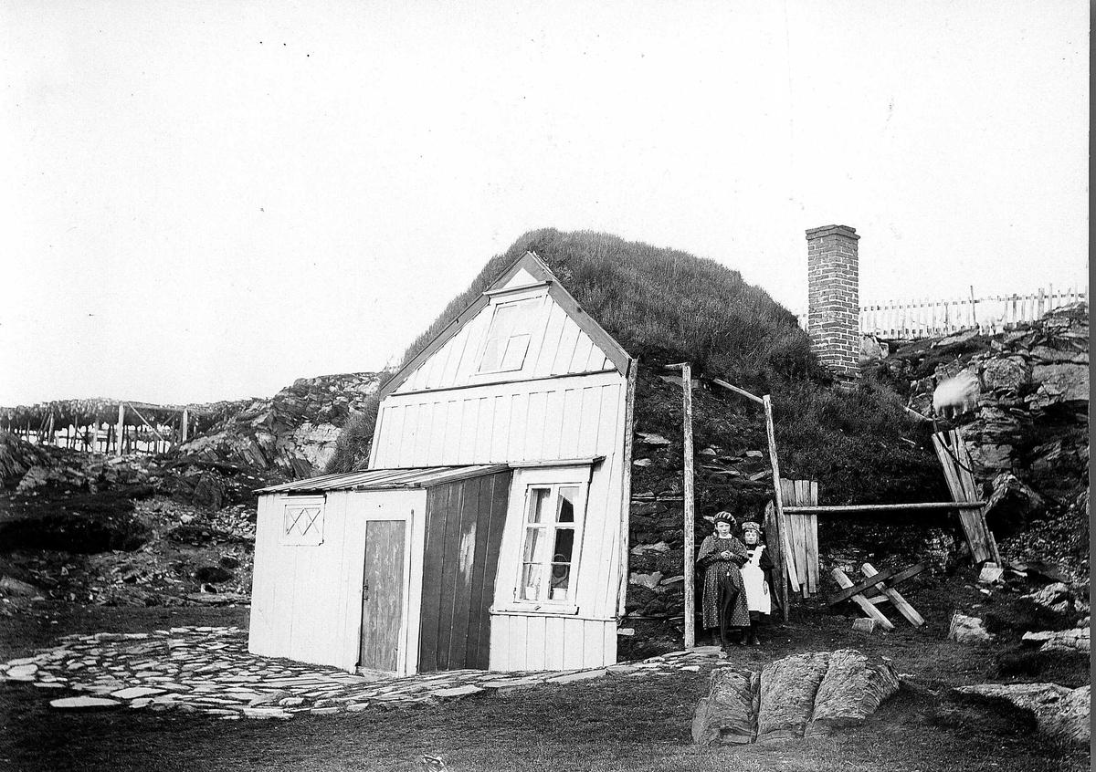 Bolighus, ukjent sted, med panelt gavlside med steinvegger bygget inn mot fjellvegg. To jenter står utenfor, den ene med en paraply i hånda. Serie tatt av Robert Collett (1842-1913), amatørfotograf og professor i zoologi.