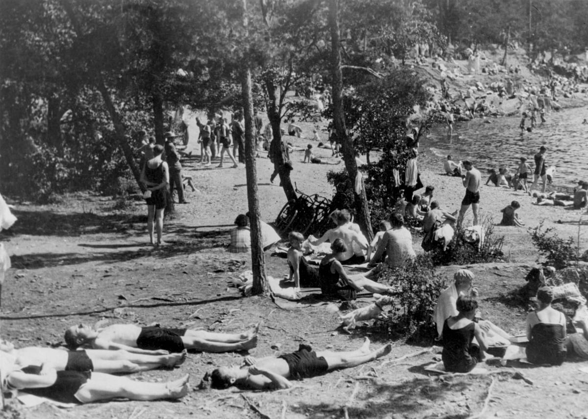 Badeliv i Paradisbukta, Oslo. Kvinner i badedrakt og menn i shorts soler seg og bader i sjøen.
