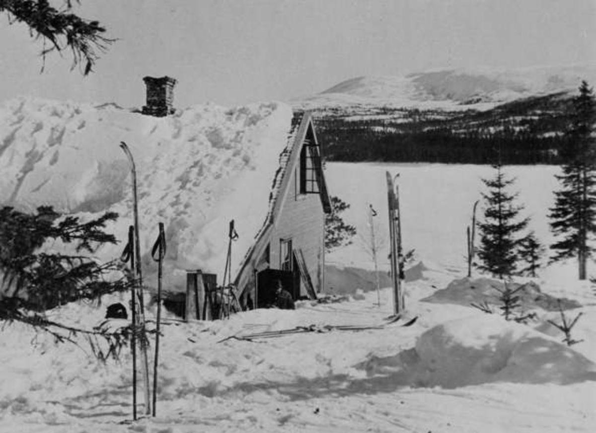 Snødekt vinterlandskap. Ski og staver står oppstilt i snøen utenfor en hytte. I bakgrunnen sees et vann og fjell.