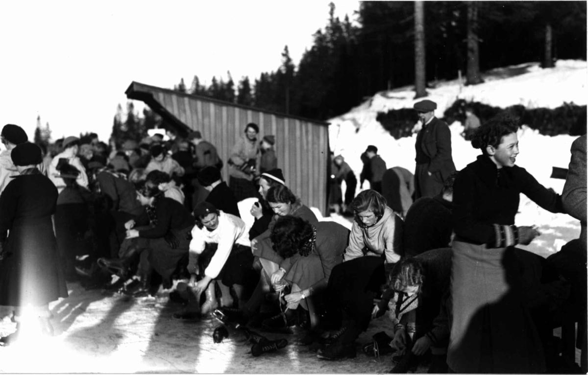 Tryvann skøytebane 1934. Unge og gamle i ferd med å ta på seg skøyter.