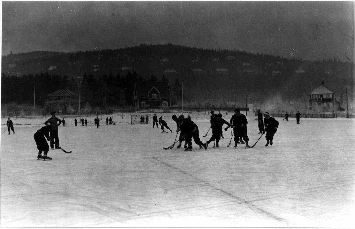 Skøyter. 1935. Bandy spilles på Gressbanen. Holmenkollåsen i bakgrunnen.