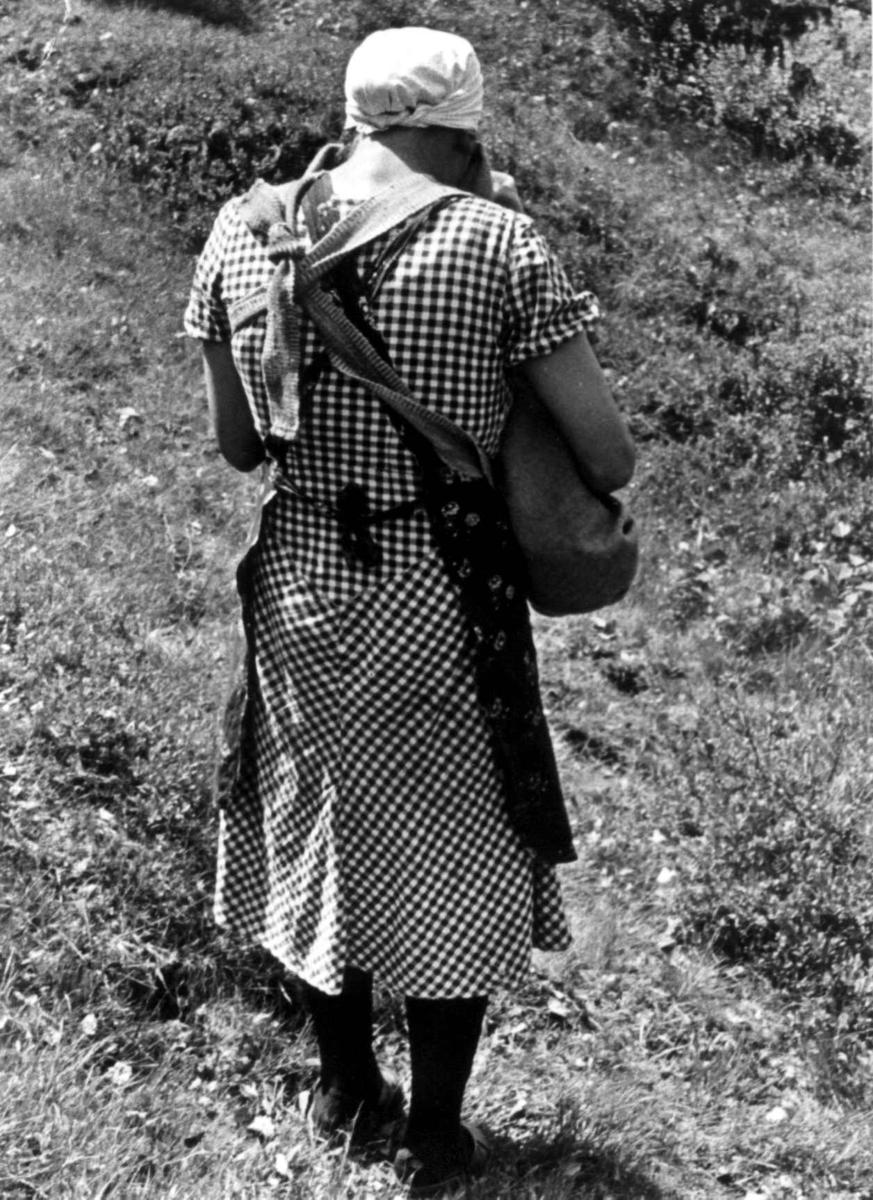 Ingeborg bærer et barn i linde på Engedal. Fjotland, Kvinesdal 1941.