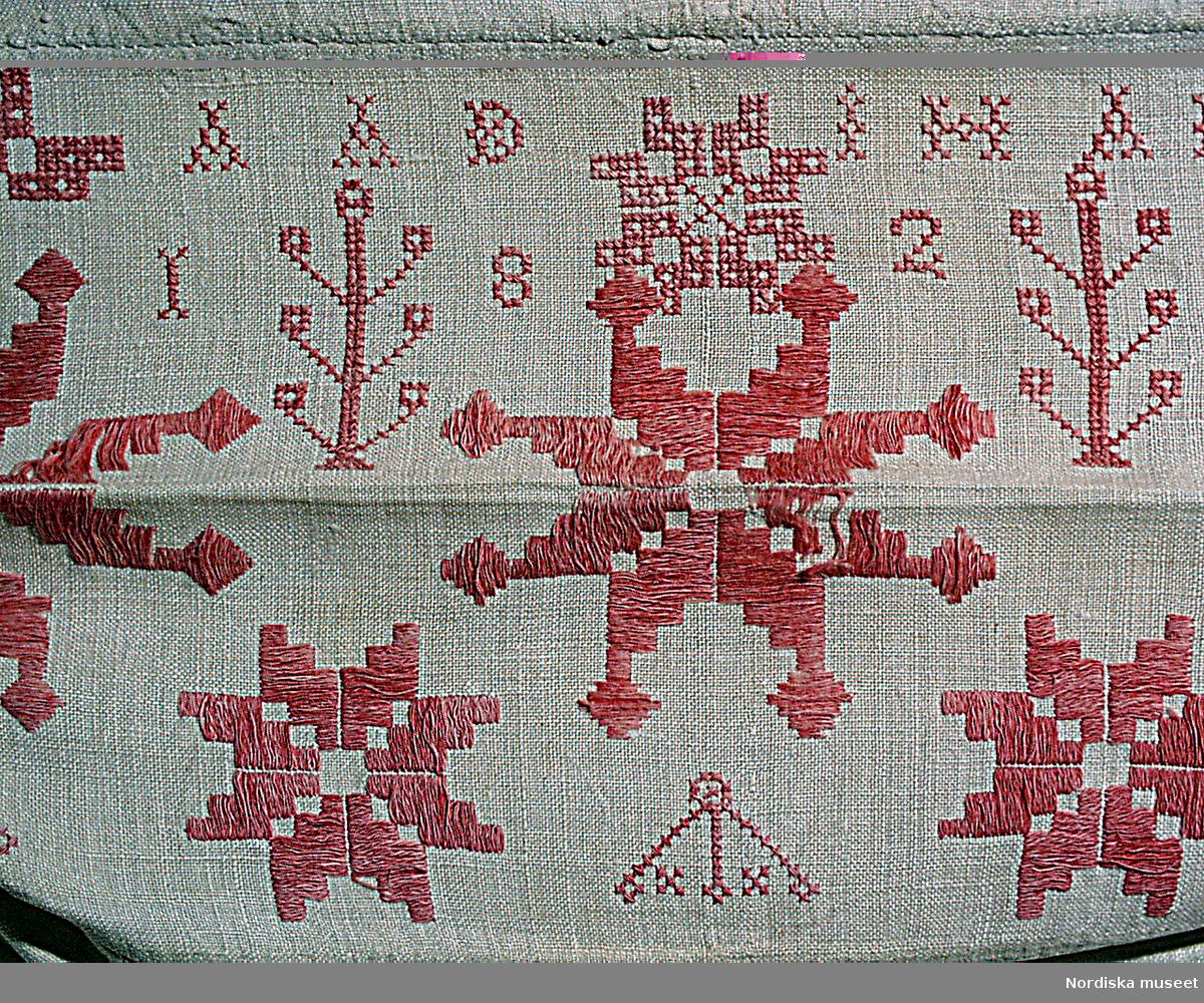 """Långörngott av vit linnelärft, öppning i ena kortsidan, i den andra fastsydd broderad """"huva"""". 3 åttauddiga stjärnor i rad samt 4 mindre, sydda i rätlinjig, ensidig plattsöm med utfyllnadsfigurer i korssöm med rosarött entrådigt bomullsgarn s.k. """"turskiskt garn"""" efter den turkisk.t röda färgen på garnet.  Huvan märkt A A D I HAMRE 1822 med det rosaröda garnet i korssöm. Denna typ av rätlinjigt broderi var vanligt i Hälsingland under tiden ca1810-1830 innan det fria broderiet i form av tofssöm och långsöm blev modernt på 1840-talet. Byns namn Hamre har här kommit med vid märkningen. Hamre ligger nära Myra by. /Berit Eldvik april 2005"""