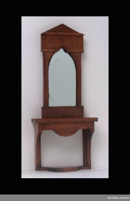Inventering Sesam 1996-1999: Spegel   H 21  B  10   (cm) Bord      H 13,5  H 11  (cm) a) Spegel av brunbetsad björk, empire med nygotiska stildrag.  b) spegelbord av brunbetsad björk. Tillhör dockskåp 151.825. Birgitta Martinius 1996