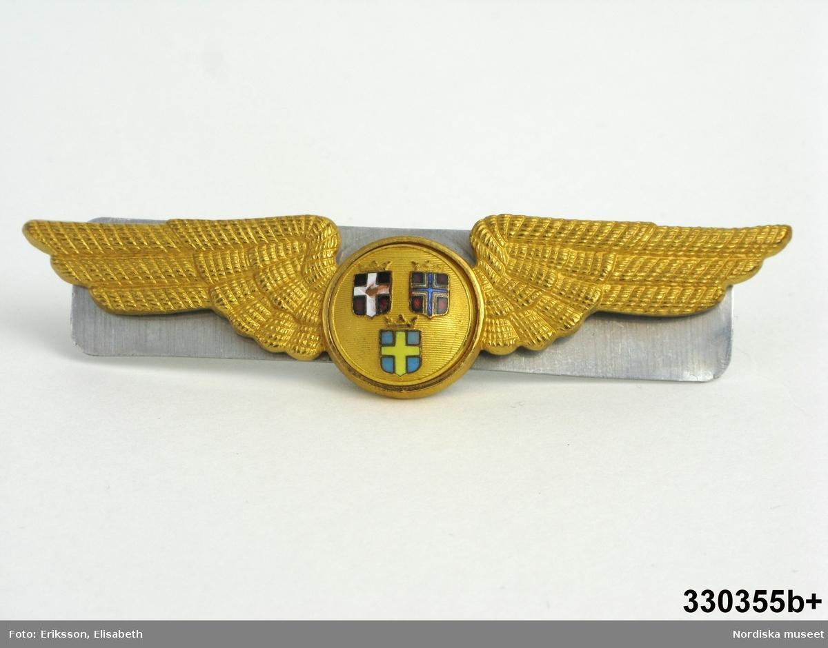 Jacka till flygvärdinneuniform, SAS, 1957 års modell. Mörkblått ylletyg, gabardin, i figursvängd kavajbetonad jacka med mjukt rundade krage och slag. Enkelknäppt med tre stycken isydda mässingsknappar med SAS emblem. Fastskruvat märke s.k. vinge i brösthöjd å vänster sida. Framstycken med vardera två delningssömmar, den främsta svänger av mot inskuren ficka. Bakstycke med mittsöm och två delningssömmar å varje sida. Sidsömmar.Isydd tvåsömsärm. Foder av mörkblått siden. Ärmfoder och fodernederkant sytt för hand. /Ingrid Roos 2010-05-04